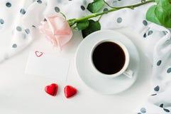 Fond de jour de valentines de St - la tasse de café, s'est levée, masque la carte d'amour et deux sucreries en forme de coeur rou Image stock