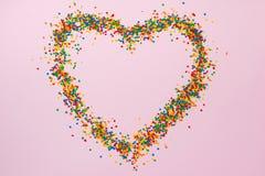 Fond de jour de valentines Forme de coeur avec des sucreries sur le rose Image libre de droits