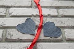 Fond de jour du ` s de Valentine de deux coeurs de denim du mur de briques blanc Images stock