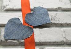 Fond de jour du ` s de Valentine de deux coeurs de denim du mur de briques blanc Photographie stock libre de droits