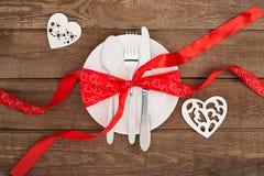 Fond de jour du ` s de Valentine, plat blanc, fourchette, couteau, coeurs de bande, coeur deux sur la vieille table en bois Images libres de droits