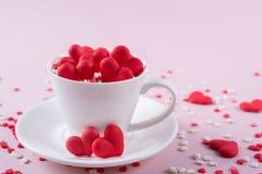 Fond de jour du ` s de Valentine Beaucoup de petit coloré arrose des coeurs dans une tasse Image libre de droits