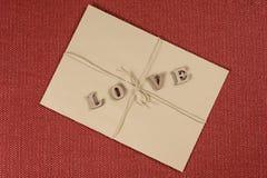 Fond de jour du ` s de Valentine, enveloppe brune de papier d'emballage avec l'amour de mot Photo stock