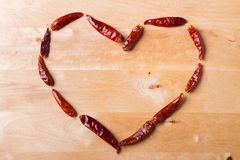 Fond de jour du ` s de Valentine Le signe du coeur est présenté des poivrons de piment d'un rouge ardent sur un fond en bois Amou Image libre de droits