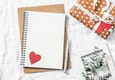 Fond de jour du ` s de Valentine Videz le carnet vide, le boîte-cadeau, fleurs sur un fond blanc, vue supérieure L'espace libre Images stock