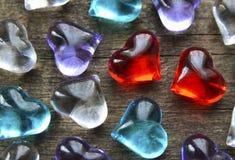Fond de jour de valentines avec les coeurs en verre colorés Deux coeurs en verre transparents rouges parmi beaucoup d'autres Jour Photos libres de droits