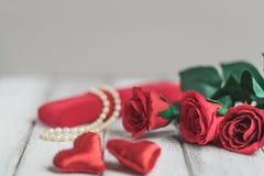 Fond de jour de valentines avec les roses, le boîte-cadeau avec la perle et deux coeurs rouges Photos stock
