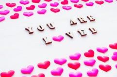 Fond de jour de valentines Les coeurs et l'inscription en soie vous êtes aimé sur le fond en bois blanc Photos libres de droits