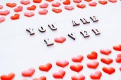 Fond de jour de valentines Les coeurs et l'inscription rouges vous êtes aimé sur le fond en bois blanc Photographie stock libre de droits