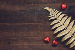 Fond de jour de valentines, maquette avec les bonbons au chocolat rouges à forme de coeur et feuilles d'or sur le fond en bois Va image libre de droits