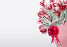Fond de jour de valentines Tulipes rouges dans le sac à provisions décoré de l'arc, du ruban et des coeurs r roman images stock