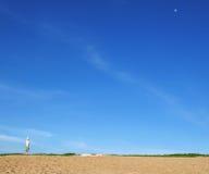 Fond de l'homme dans la chemise blanche, le chapeau blanc et le pantalon vert sur une colline de sable Images stock
