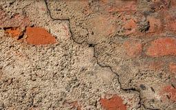 Fond de la plaine grise de mur de ciment texturisée avec une fente diagonalement avec des éléments de brique rouge Image stock