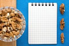 Fond de menu Cuisinier Book Carnet de recette avec des noix sur un fond bleu Photographie stock libre de droits