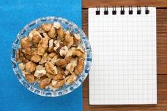 Fond de menu Cuisinier Book Carnet de recette avec des noix sur un fond bleu et un conseil en bois Images stock