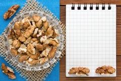 Fond de menu Cuisinier Book Carnet de recette avec des noix sur un fond bleu et un conseil en bois Photos stock
