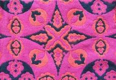 Fond de modèle tissé par coton géométrique Contexte de kaléidoscope Ornement abstrait dans des couleurs noires, rouges, et roses Images stock