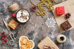 Fond de Noël avec des boîtes de présents, chocolat chaud, biscuits sur le fond rustique Fabrication des cadeaux faits maison pour photographie stock libre de droits