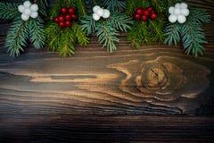 Fond de Noël avec des branches et des baies de sapin sur le conseil en bois grunge Copiez l'espace Photos libres de droits