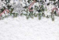 Fond de Noël avec des cannes de sucrerie, des ornements et des flocons de neige Photographie stock
