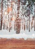 Fond de Noël avec des sapins et fond brouillé de l'hiver avec le Joyeux Noël des textes et la bonne année et la table en bois photos stock