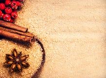 Fond de Noël avec du sucre roux, l'étoile et la cannelle s d'anis Photographie stock