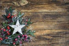 Fond de Noël avec l'étoile blanche, les branches de sapin et la décoration rouge de baies Image stock