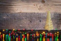 Fond de Noël avec l'arbre de décorations et lumières sur le te en bois Photographie stock libre de droits