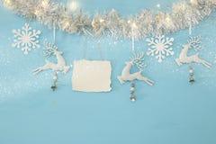 Fond de Noël avec la guirlande de fête d'arbre, les cerfs communs blancs, et les flocons de neige blancs de papier au-dessus du f Photo libre de droits