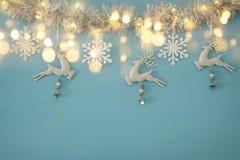 Fond de Noël avec la guirlande de fête d'arbre, les cerfs communs blancs, et les flocons de neige blancs de papier au-dessus du f Photographie stock
