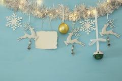 Fond de Noël avec la guirlande de fête d'arbre, les cerfs communs blancs, et les flocons de neige blancs de papier au-dessus du f Image libre de droits