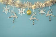 Fond de Noël avec la guirlande de fête d'arbre, les cerfs communs blancs, et les flocons de neige blancs de papier au-dessus du f Photos stock