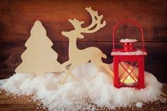 Fond de Noël avec la lanterne rouge, le renne décoratif en bois et l'arbre sur la neige au-dessus du fond en bois photographie stock libre de droits