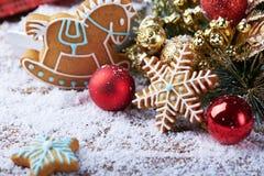 Fond de Noël avec la neige, la décoration rouge d'hiver et les biscuits de flocon de neige Photo libre de droits