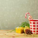 Fond de Noël avec la tasse et décorations au-dessus de fond rêveur de tache floue Image stock
