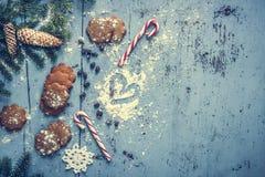 Fond de Noël avec le pain d'épice, la canne de sucrerie, le coeur et l'arbre de sapin Photographie stock