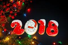 Fond de Noël avec le pain d'épice, les arbres de Noël et les lumières Photos stock
