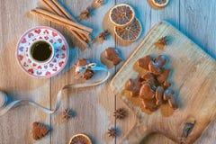 Fond de Noël avec le pain d'épice sur le panneau en bois et la tasse de café, ingrédients de cuisson avec le pain d'épice Images stock