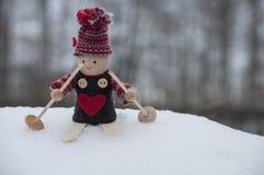 Fond de Noël avec le petit nain dans le chapeau tricoté sur des skis dans le paysage neigeux dans le temps de Noël Photo stock