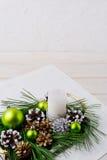 Fond de Noël avec le pinecone neigeux et les ornements verts Image libre de droits