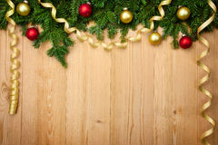 Fond de Noël avec le sapin, les babioles et les rubans sur le bois Image stock