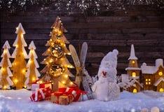 Fond de Noël avec le village et le bonhomme de neige en bois lumineux image libre de droits