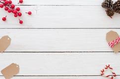 Fond de Noël avec les étiquettes de Noël, la baie de houx, le contre de pin et la canne de sucrerie sur le fond en bois blanc Image libre de droits