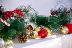 Fond de Noël avec les boules d'or et les branches rouges de sapin Carte de voeux images stock