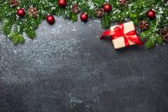 Fond de Noël avec les branches, le boîte-cadeau et les décorations de sapin images libres de droits