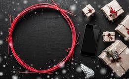 Fond de Noël avec les cadeaux et l'espace de téléphone portable et l'espace pour le message de Noël pour ceux près du bakgraund Image stock
