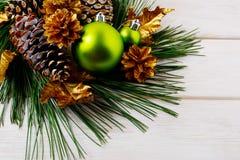Fond de Noël avec les ornements verts et les cônes d'or de pin Images stock