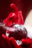 Fond de Noël avec une boule en verre brillante sur les mains modèles Chr Photo stock