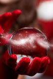 Fond de Noël avec une boule en verre brillante sur les mains modèles Chr Image stock