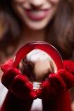 Fond de Noël avec une boule en verre brillante sur les mains modèles Chr Photo libre de droits